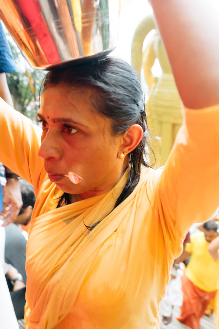 A Hindu devotee carrying a pot of milk with her tongue pierced