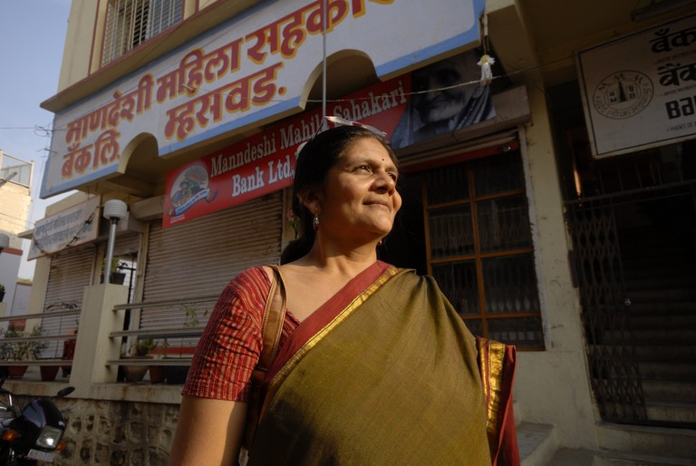 Ms. Chetna Vijay Sinha with bank in the background