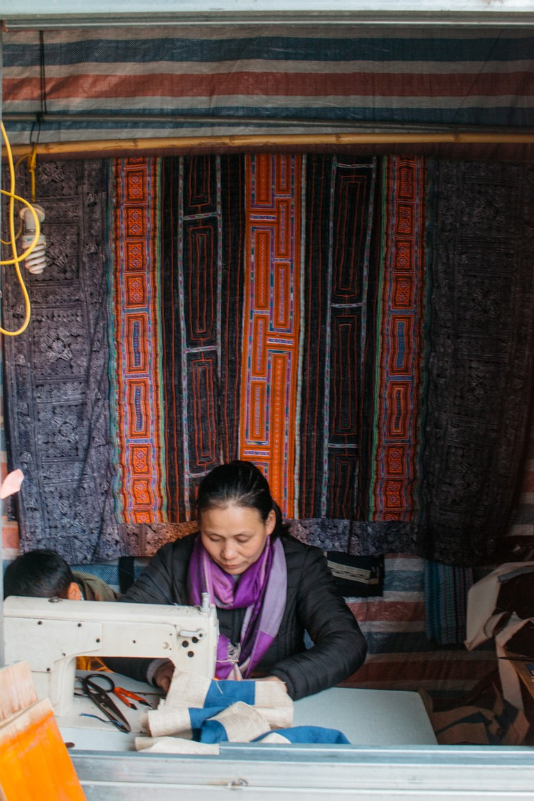 You will see women stitching colorful pieces of brocade.