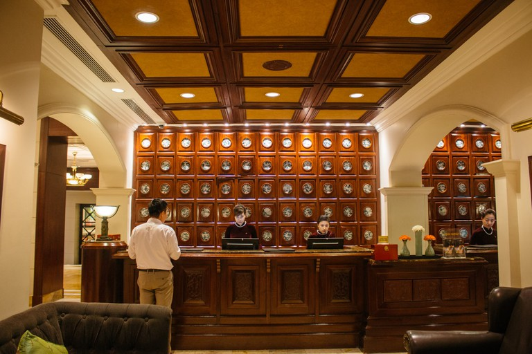 The concierge desk wrapped in rich mahogany