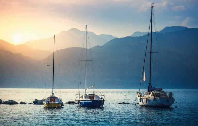 Sailing boats float in the Malcesine marina on Lake Garda | Shutterstock/Yasonya