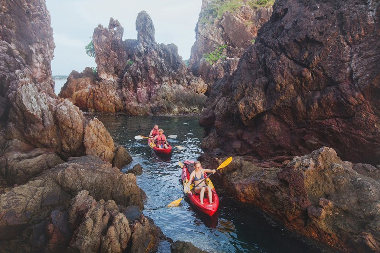 Kayaking between the sea cliffs at Koh Mak, Thailand