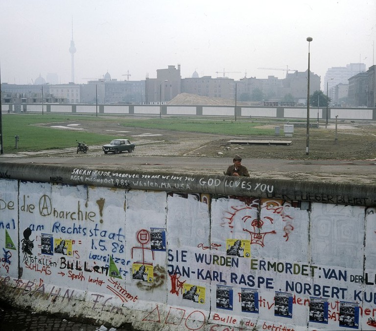 Berlin Wall, East German border guard looks out at the Kubat-Dreieck