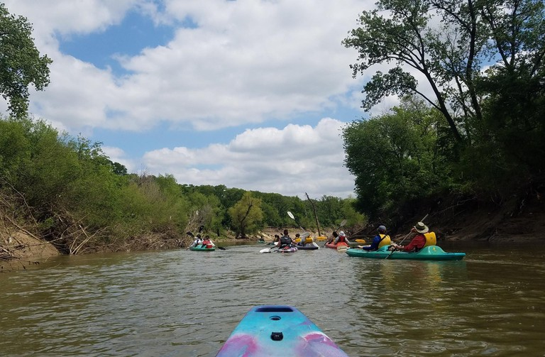 Kayakers paddling down the Trinity River with Trinity River Audubon Center