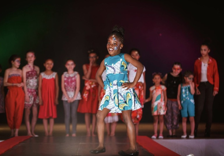 A young girl proudly modeling during the Nuit du Costume Africain