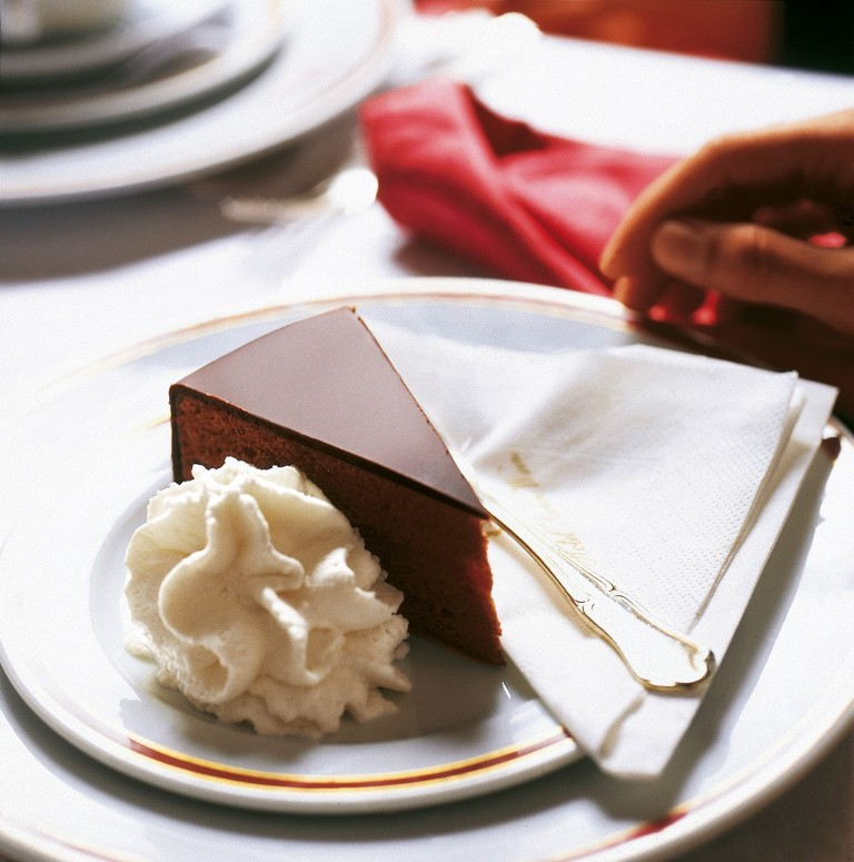 A gorgeous piece of Sachertorte with a serving of whipped cream