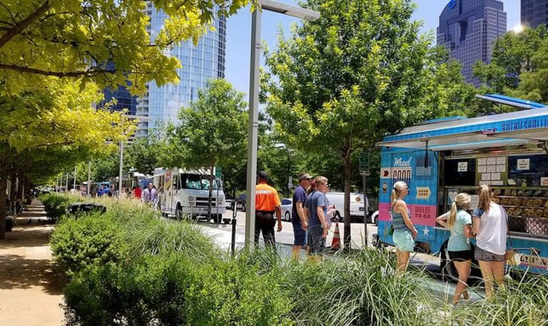 Visitors to Klyde Warren Park grab food from a line of food trucks