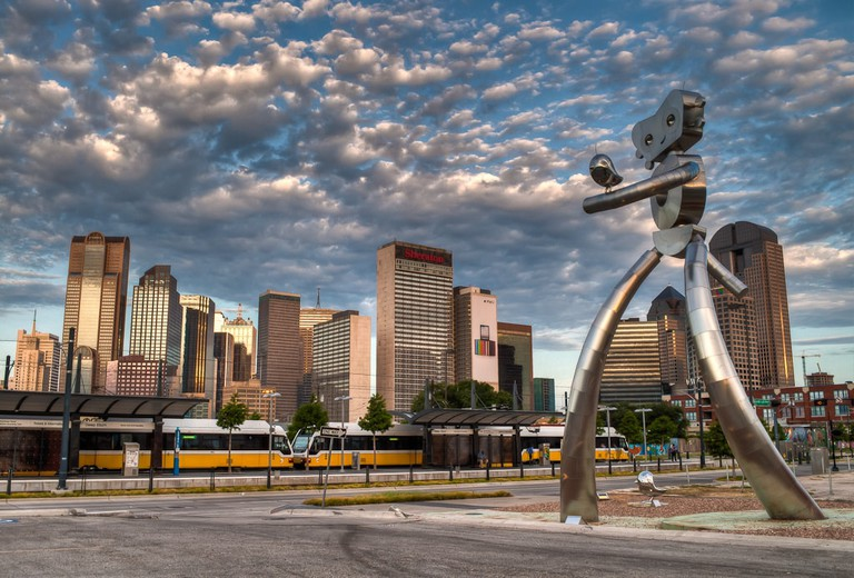 'Standing Tall' shows the Traveling Man walking toward the Deep Ellum Rail Station