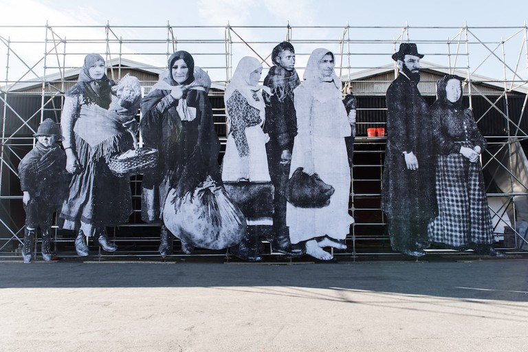 JR's 'So Close,' presented by Artsy and Jeffrey Deitch at the entry to Pier 94, replaces the faces of immigrants passing through Ellis Island with those of current Syrian refugees. Image courtesy of The Armory Show