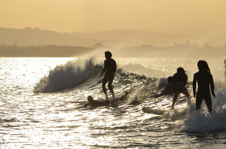 Surfers riding the waves of Byron Bay