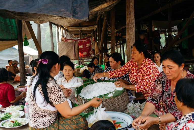 Women prepare a feast beneath their houses during dry season