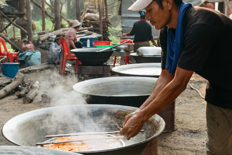 A villager cooks local snacks