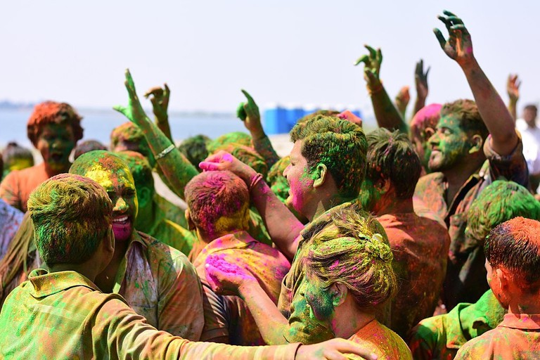People playing with colors and dancing in Holi