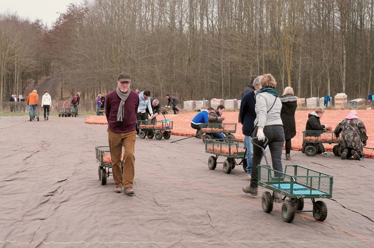 Volunteers help put the clay sculptures in place.