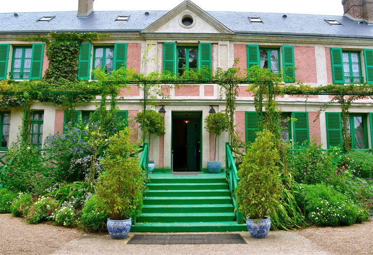 The salmon-pink and green facade of Monet's humble home