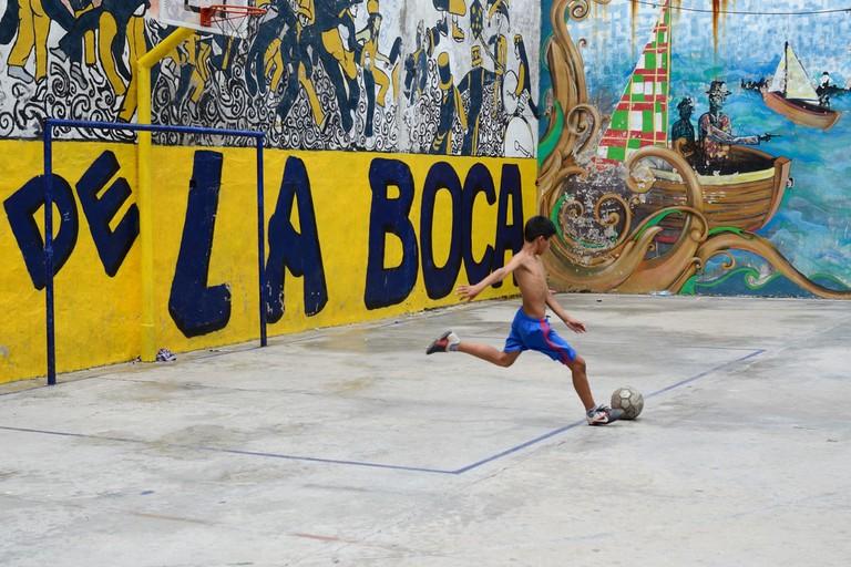 A kid playing football in La Boca