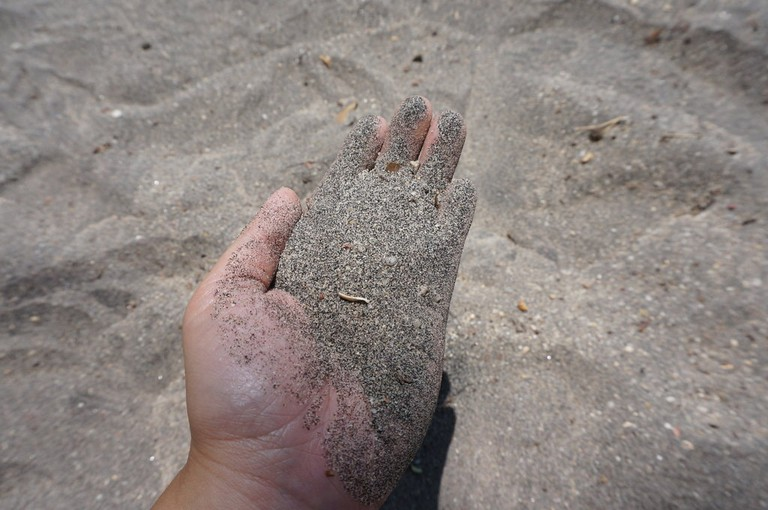There is no exact answer to why the sand is black on Pantai Pasir Hitam | © Sam Bedford
