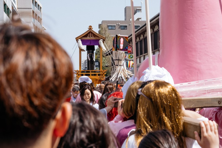 Groups of participants carry the shrines down the street