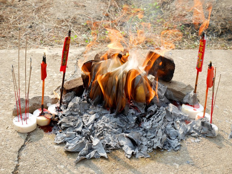 Ancestor offering burning at grave site on Tomb Sweeping Day | © p_saranya/Shutterstock