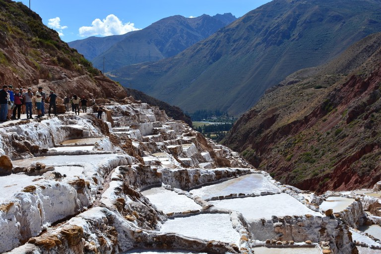 Tourists visiting the old Inca salt fields of Maras, in Cuzco, Peru