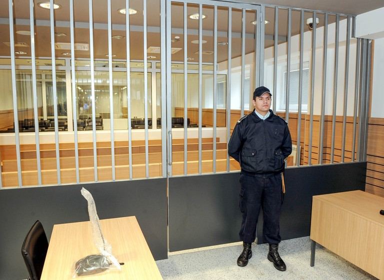 Police officer guards prison courtroom, Belgrade, Serbia | © bibiphoto/Shutterstock