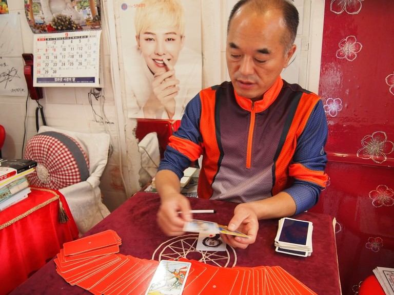 A tarot card reader gives insight into the meaning of the drawn cards.