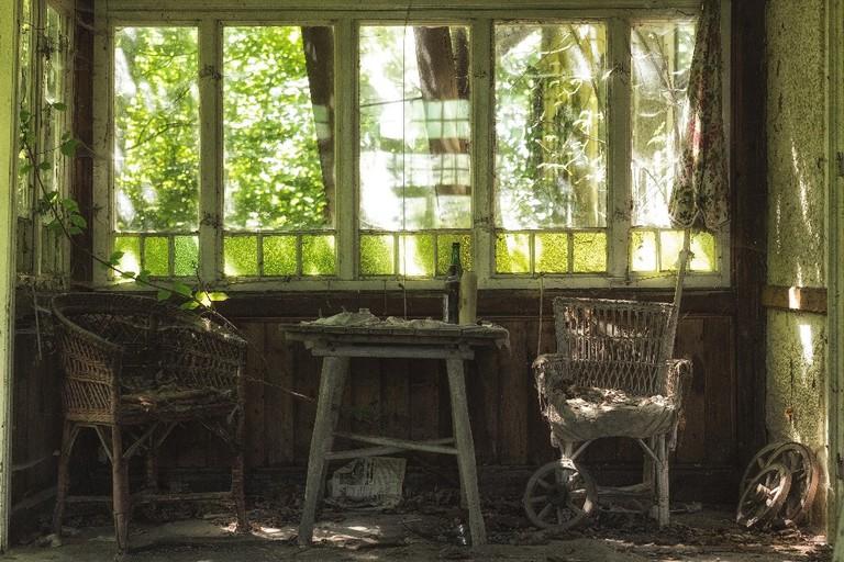 Slowly overgrowing veranda in an abandoned house