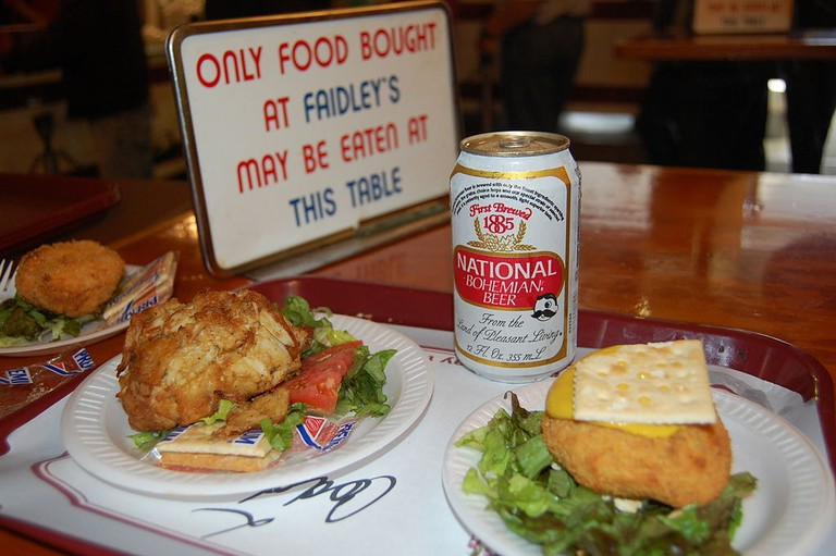 """A Faidley's coddie on the right, with a crab cake and National Bohemian """"Natty Boh"""" beer—a true Baltimore meal"""