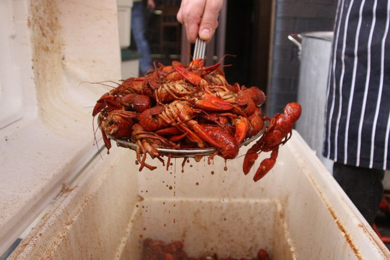 Hot boiled crawfish are often served out of giant ice chests designed to trap the heat after the crawfish leave the pot.
