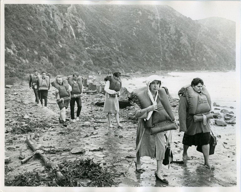 Survivors walk along the coast after being rescued from the Wahine