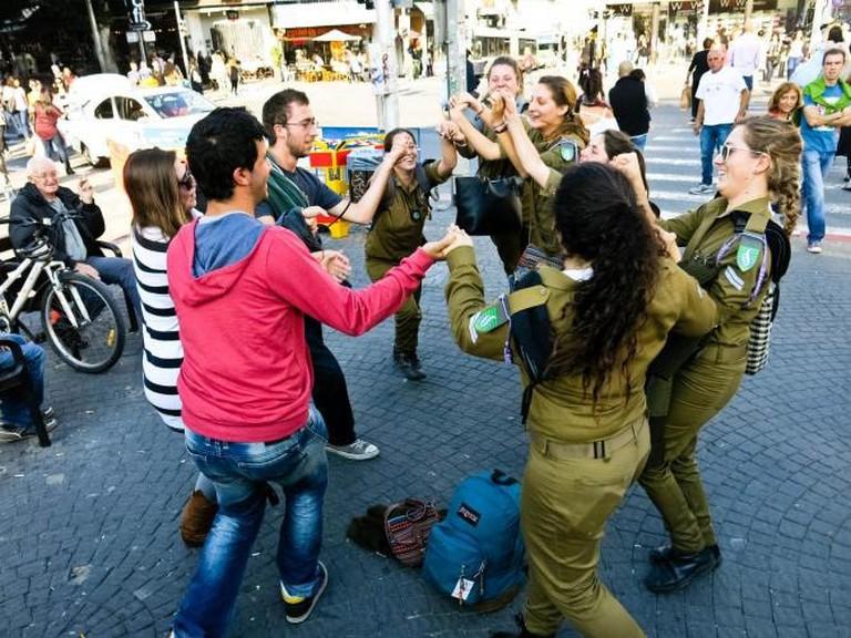 Soldiers and civilians dancing by Carmel Market, Tel Aviv