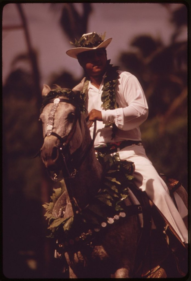 696px-COSTUMED_FOR_ALOHA_DAY_PARADE_ONE_OF_MANY_FESTIVITIES_DURING_ANNUAL_ALOHA_WEEK._HAWAIIAN_COWBOYS_CUSTOMARILY_WEAR..._-_NARA_-_553717