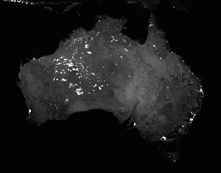 A night satellite view of Australia lit up by cities and bush fires