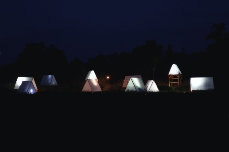 A-frame tents and micro cabins at night