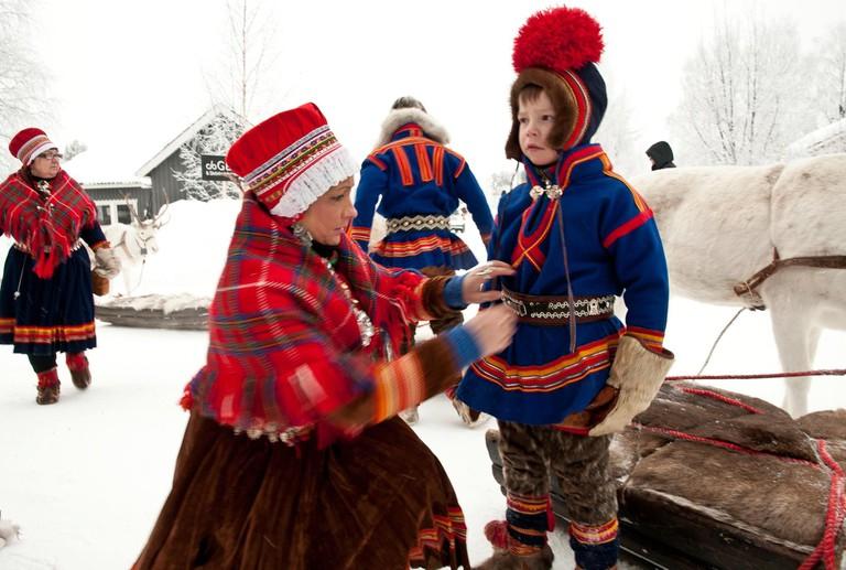 Helping a Sami boy with his kolt, © Lola Akinmade Åkerström:imagebank.sweden.se, Courtesy of Sweden.se