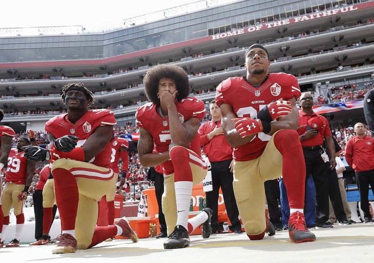 Colin Kaepernick (center) kneels during the national anthem in 2016