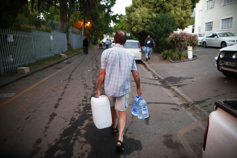 A Cape Town resident walks away with jugs of clean water