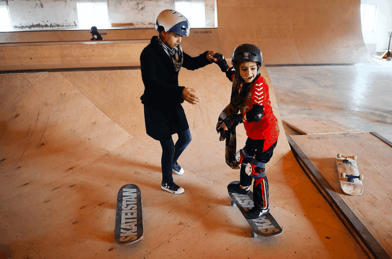 Two Skateistan children help each other during a skateboarding lesson