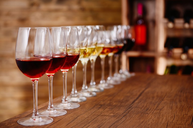 Glasses of different wine in a row on bar counter