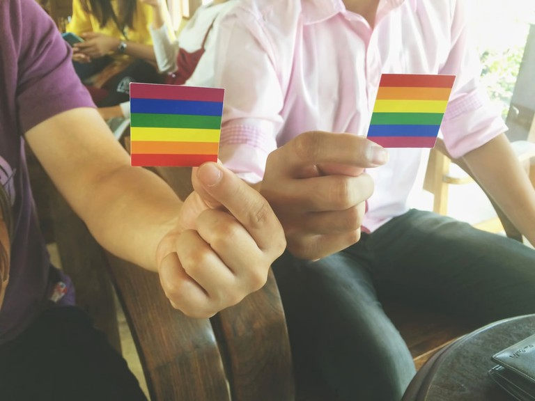 Gay couple showing LGBT flag