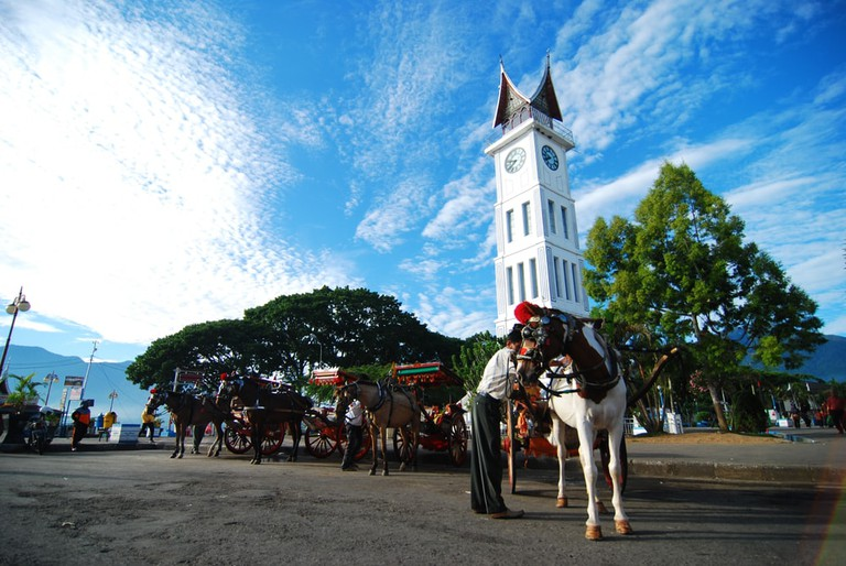Men standing next to his Bendi at Jam Gadang Bukittinggi Monument square at West Sumatra, Indonesia