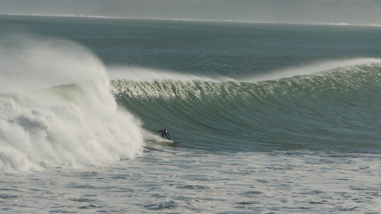 A surfer in Manu Bay, Raglan