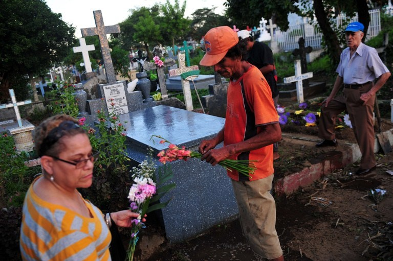 People holding flowers at the General Cemetery in Managua