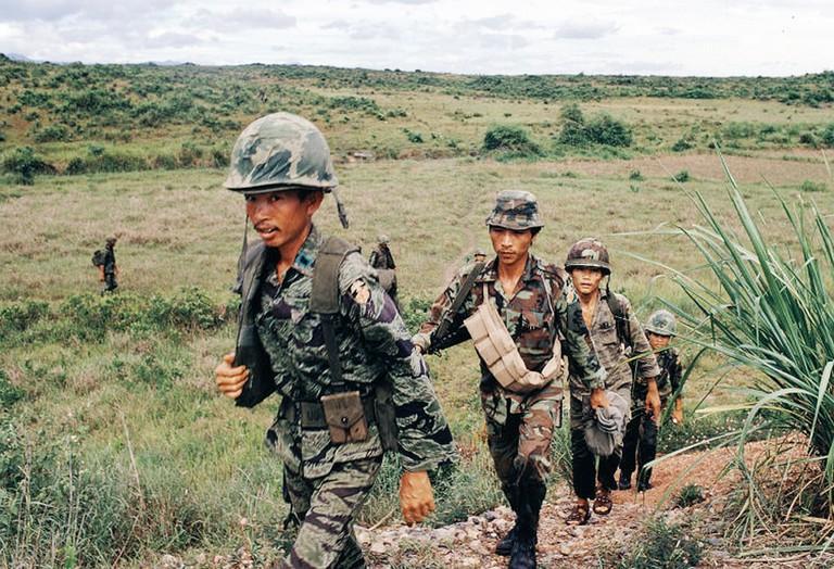 Soldiers make their way through an open field in Vietnam in 1972