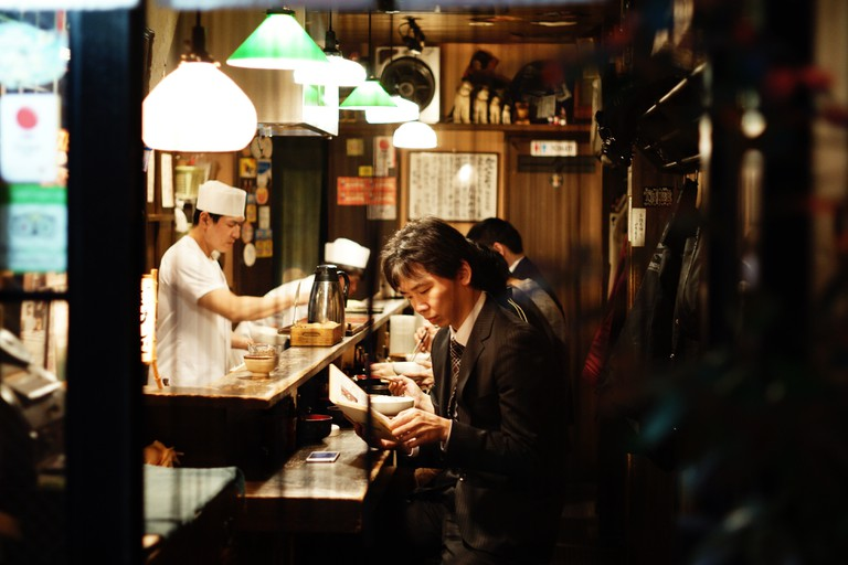 A man dines alone at a Japanese counter-style restaurant