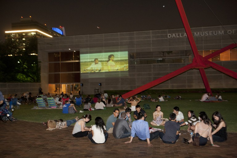 Visitors watch a film on the side of Dallas Museum of Art during their Late Nights series