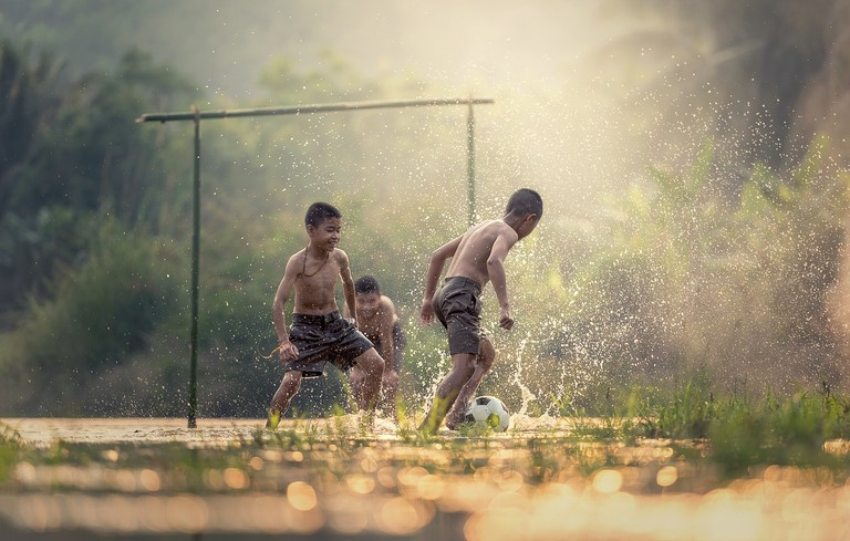 Kids playing football in the field