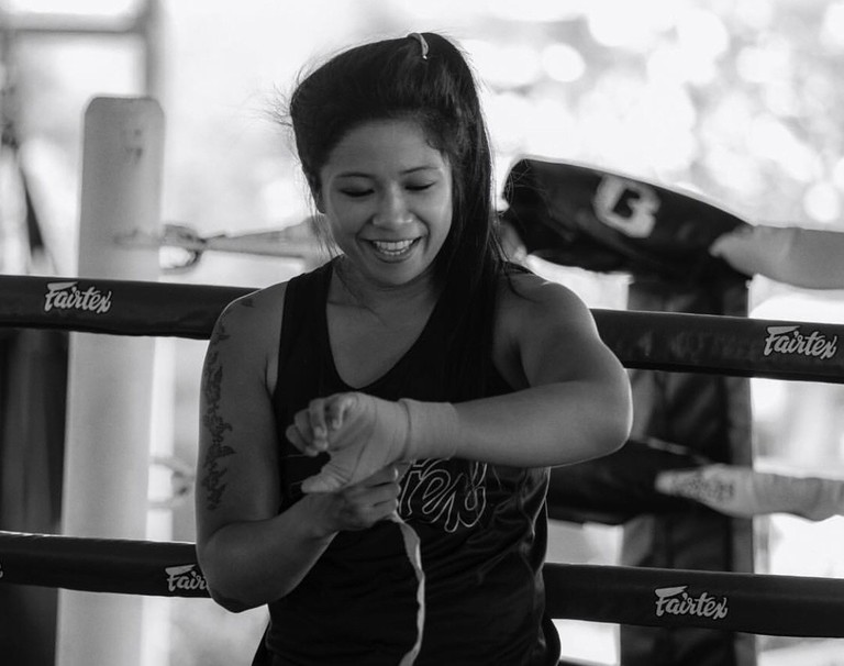KC Carlos putting on her hand wraps