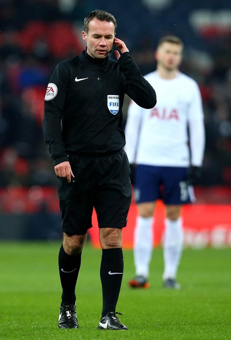 Referee Paul Tierney speaks to VAR before disallowing Érik Lamela's goal against Rochdale