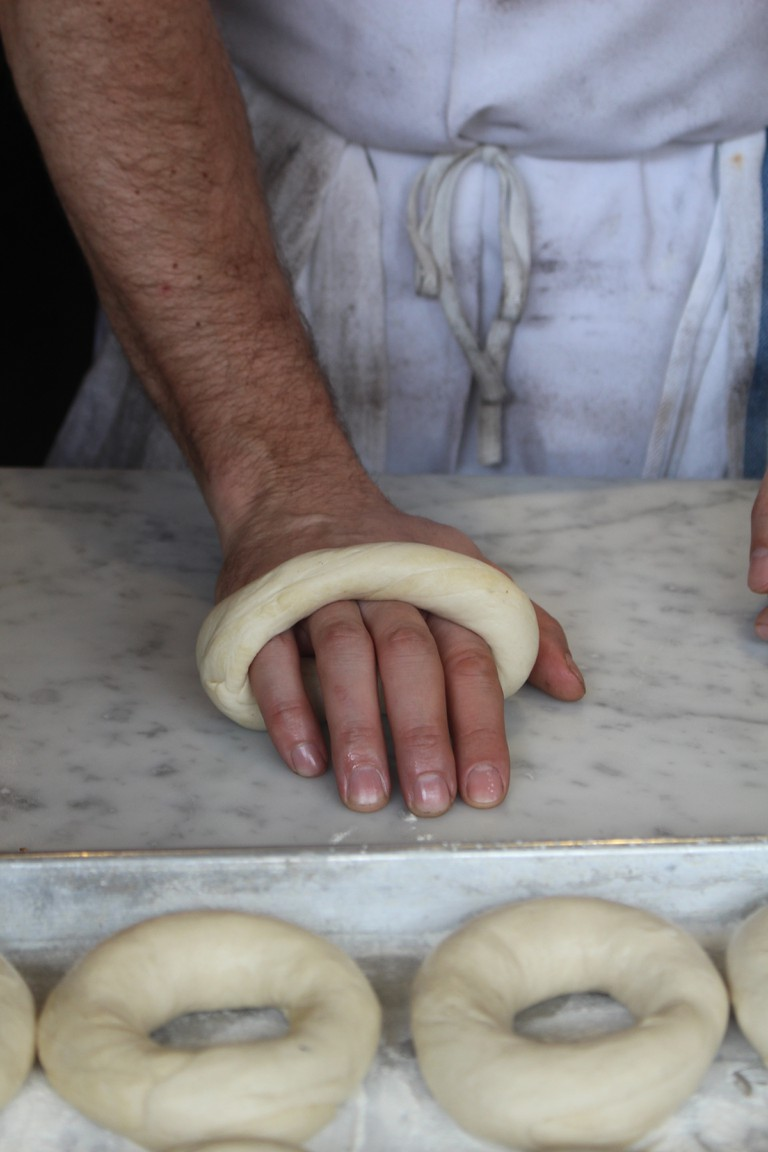 Rolling out the bagel dough.